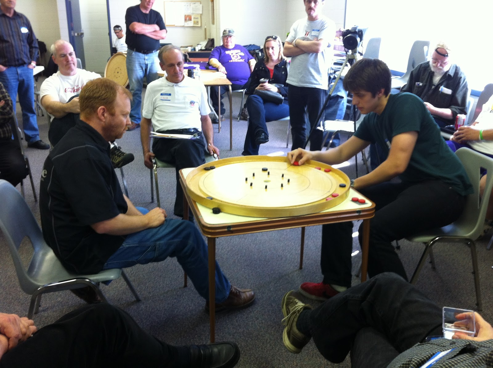 Justin Slater (right) eyes a takeout in the 2013 St. Jacobs Crokinole Tournament final against Ray Beierling (left) as the rest of the field looks on.