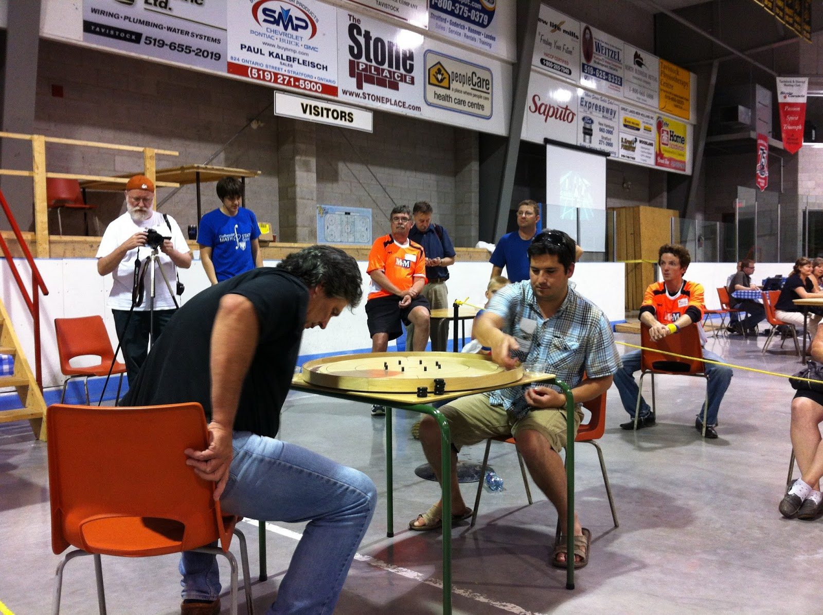 Jon Conrad adjusts his chair while Raymond Haymes collects his discs before the Championship match of the 2013 World Crokinole Championships