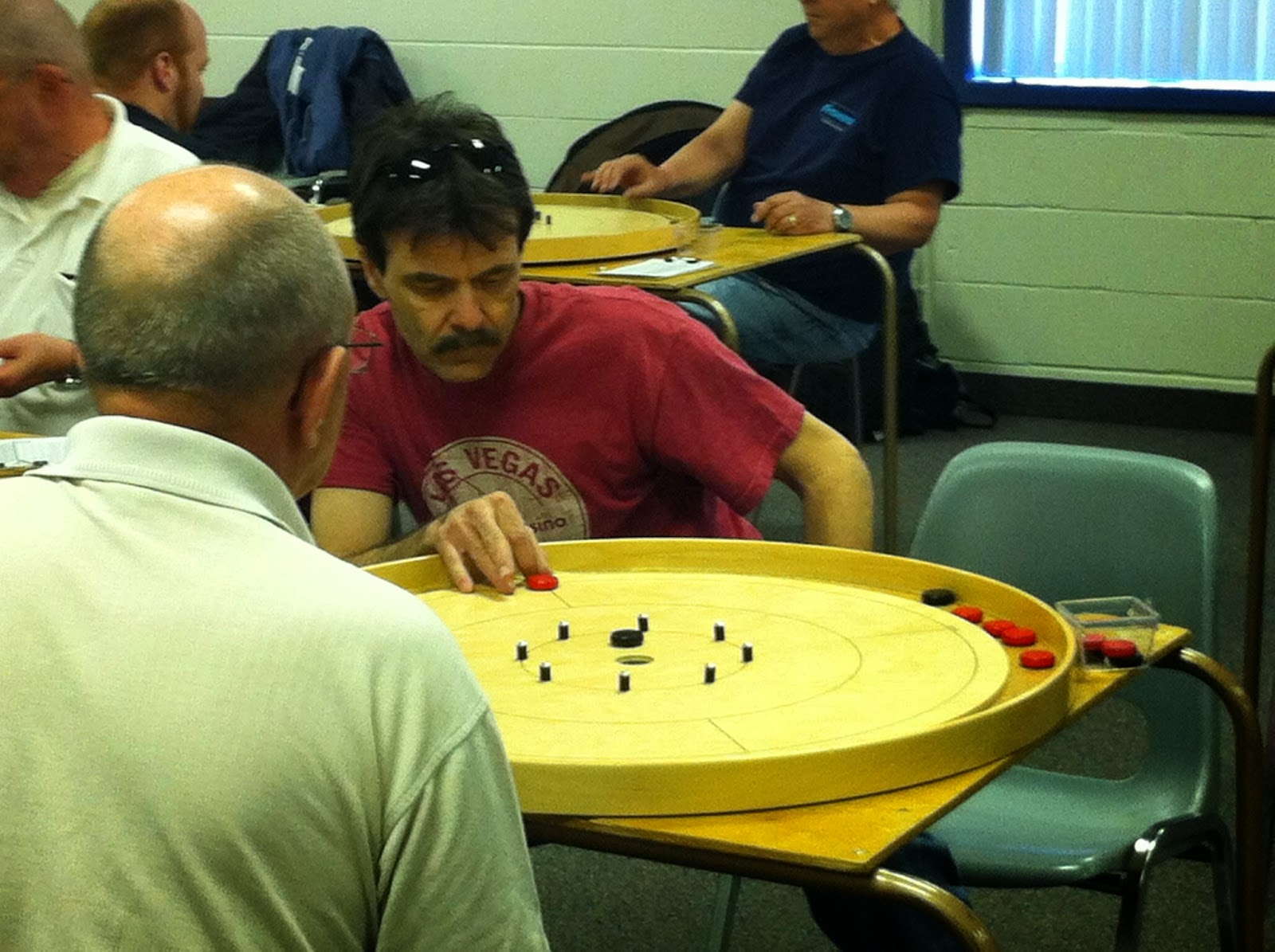 Roger Vaillancourt leans to set up for a shot during first round action at the 2014 Ontario Singles Crokinole Championship.
