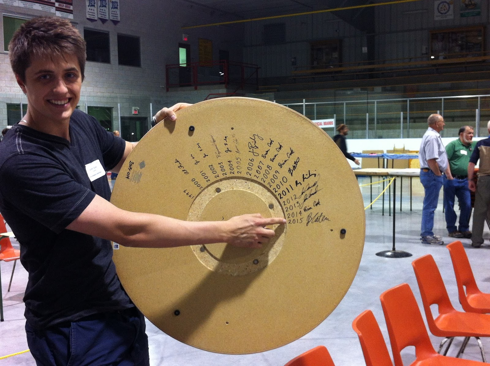 Justin Slater, 2015 World Crokinole Champion, posing with the World Champion signature board.