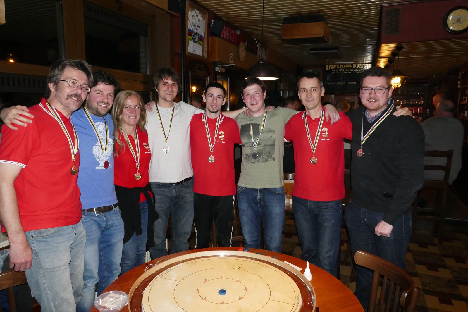 Crokinole players posing in front of a board